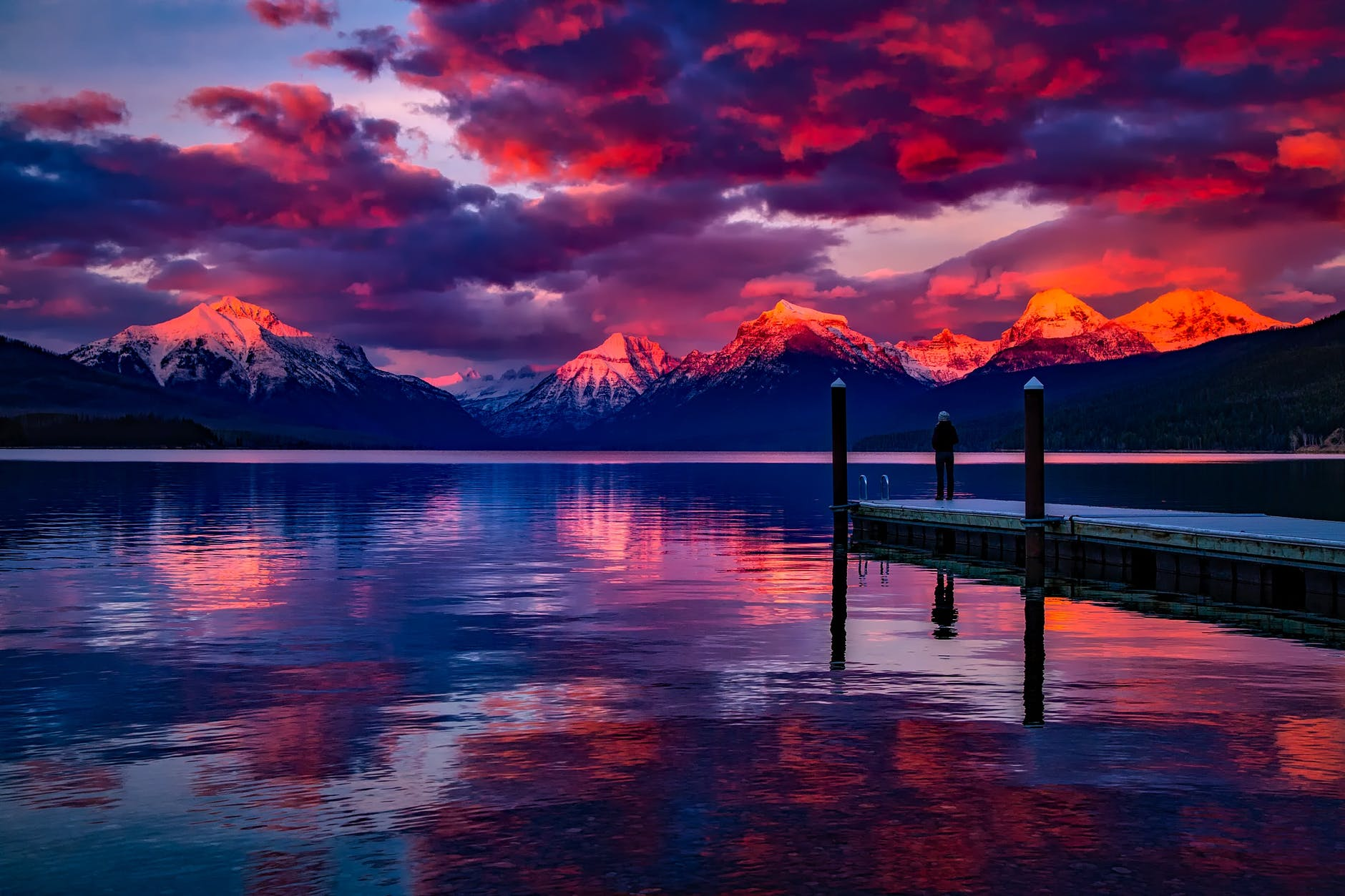 Sunset over mountains. Purple, red and orange sky. Snow-capped peaks look over a vast, still lake. A man looks at the scenic beauty on a landing near the lake.